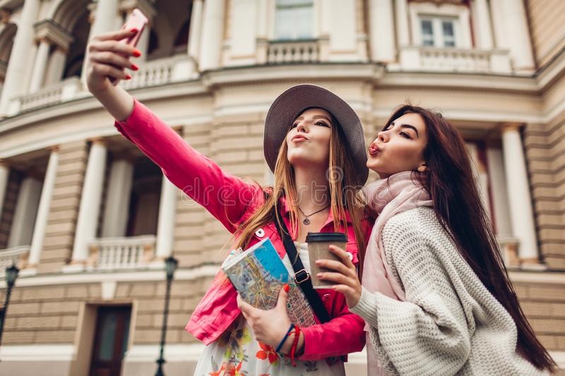 Women tourists taking selfie going sightseeing in Odessa. Happy friends travelers having fun. During vacation stock images
