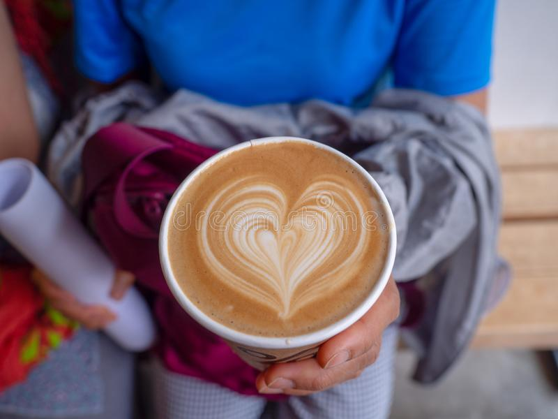 Women tourists wear a blue shirt hold hand a coffee art with heart-shape pattern.Close up cup of coffee with heart-shape pattern. Women tourists wear a blue nT stock image