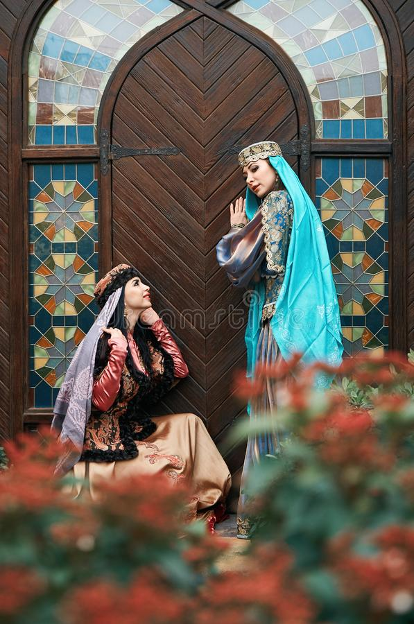 Women in traditional Azerbaijani dress knocking the wooden door of an old house stock image