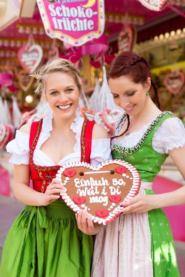 Women in traditional Bavarian clothes or dirndl on festival. Young women in traditional Bavarian clothes - dirndl or tracht -with a gingerbread souvenir heart on stock image