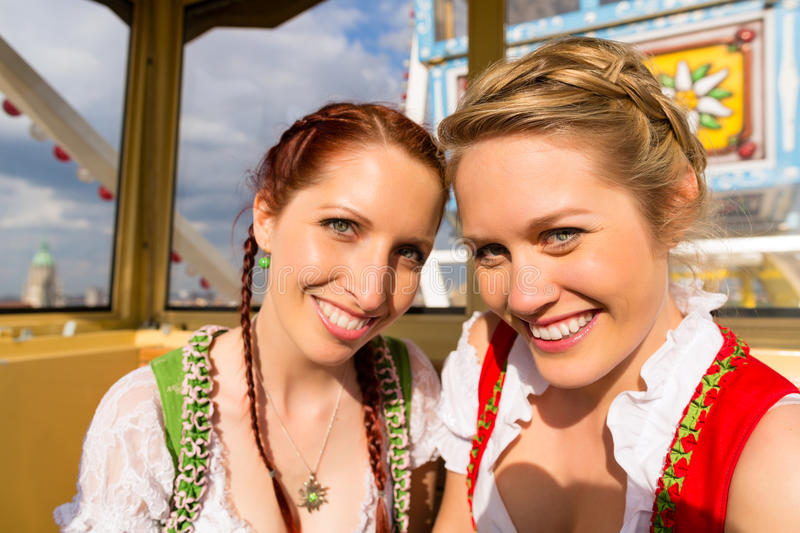 Women in traditional Bavarian dirndl on festival. Young women in traditional Bavarian clothes - dirndl or tracht - on a festival or Oktoberfest riding the ferris royalty free stock photo