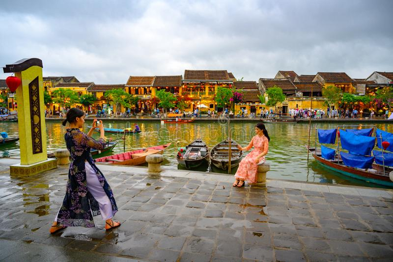 Asian women taking photos on canal in tourist destination Hoi An, Vietnamese women in Hoi An, Vietnam stock images