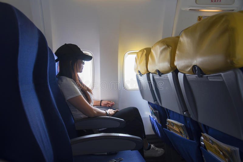 Women traveling by an airplane. Women sitting by aircraft window and looking outside. stock image
