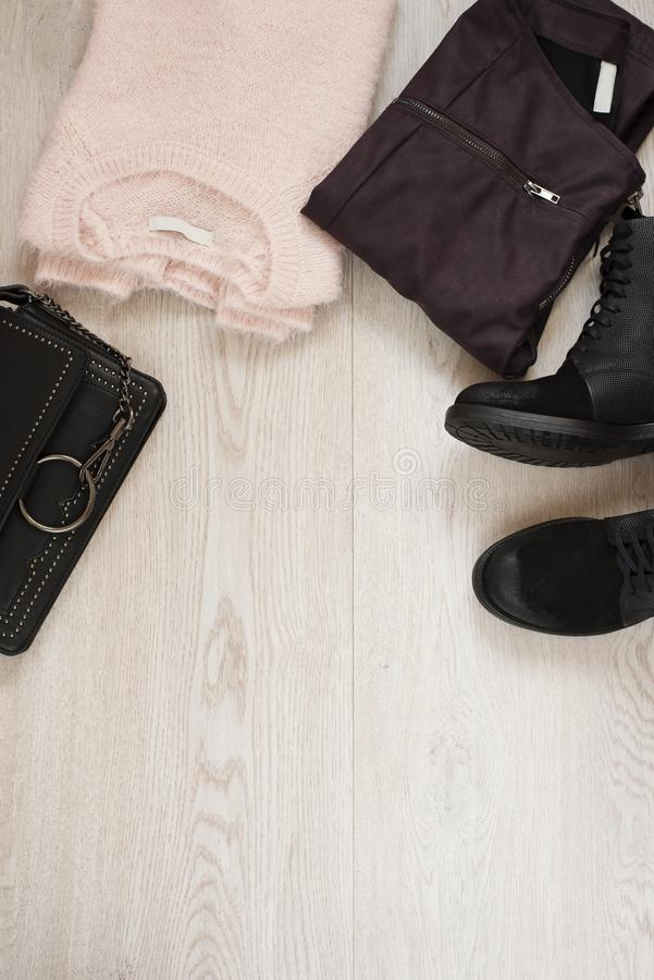 Women trendy fashion clothes collage with sweater, leather pants, military boots and bag. Flat lay royalty free stock photo