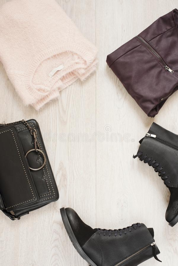 Women trendy fashion clothes collage with sweater, leather pants, military boots and bag. Flat lay royalty free stock photography