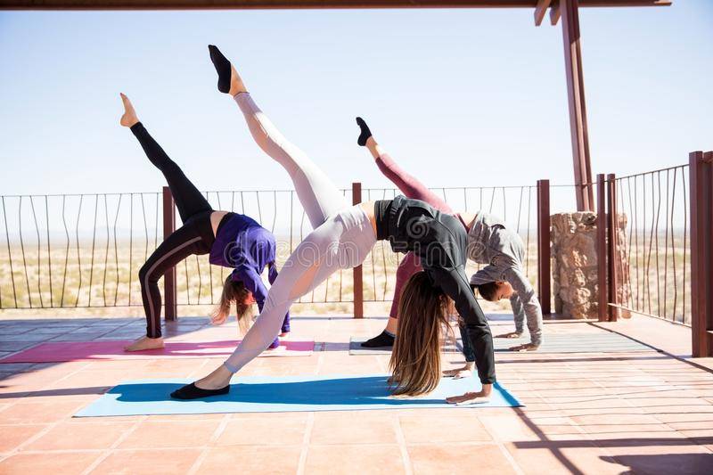 Women trying out yoga poses in class. Three young women bending backwards with leg outstretched at yoga class royalty free stock image