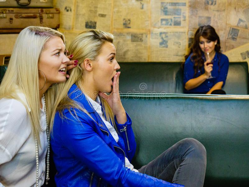 Women gossiping about friend. Women two girlfriends gossiping about third, sad girl with alcohol glass in the background. Friendship rivaly and envy problems royalty free stock photos