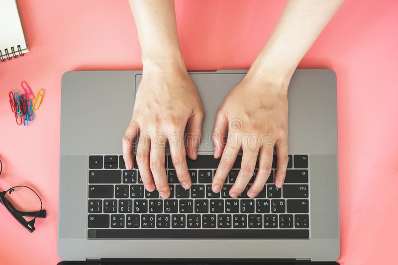 Women typing on laptop in pink pastel colourful office with accessories royalty free stock photography