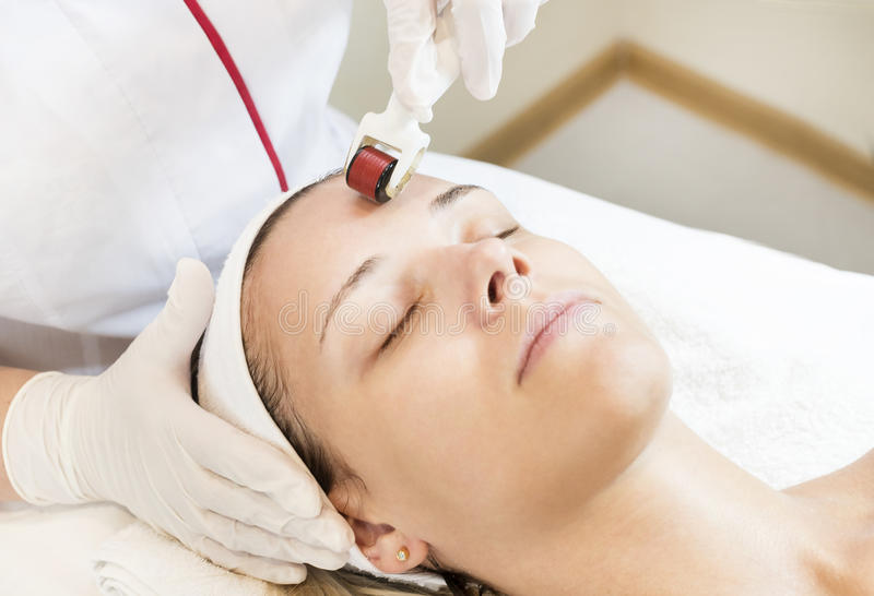 The woman undergoes the procedure of medical micro needle therapy. The women undergoes the procedure of medical micro needle therapy with a modern medical stock image