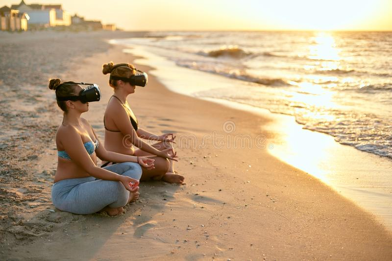 Women use VR glasses for deeper immersion. Two females doing group yoga meditation on the beach in virtual reality royalty free stock photography