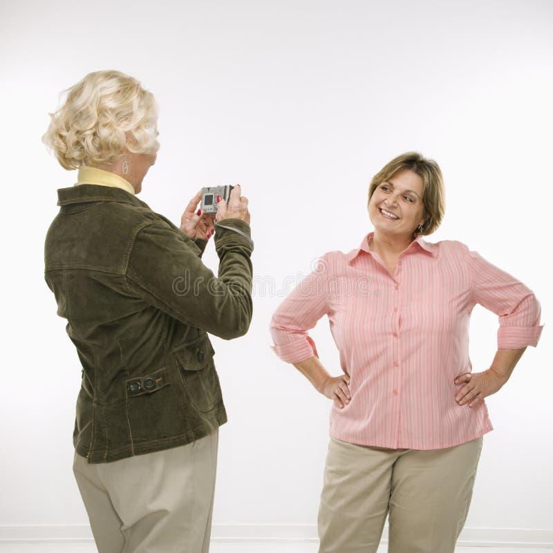 Women using digital camera. Caucasian senior woman taking photo with digital camera of middle aged woman royalty free stock photo