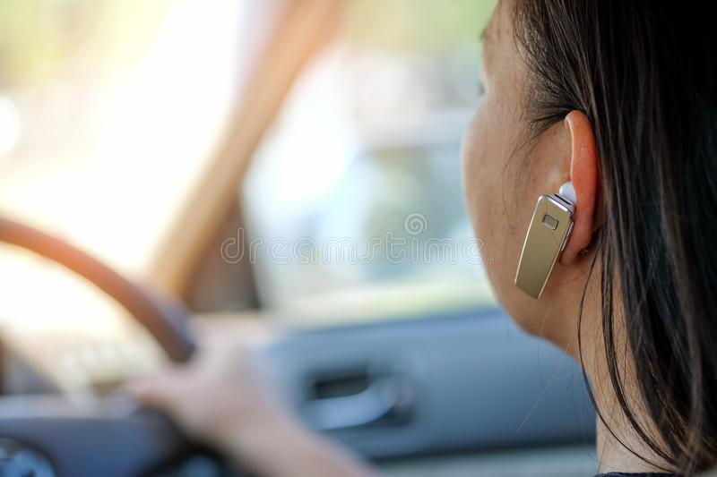 Women using hands-free phone while driving. royalty free stock photos