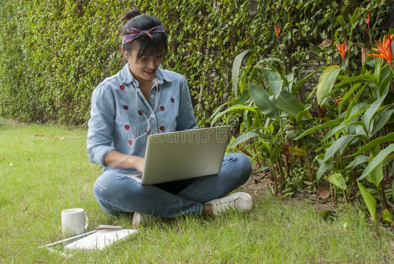 Women are using laptops in the garden. Asian woman sit on the internet using laptops in the park on holidays. With a notebook and coffee beside her stock photo