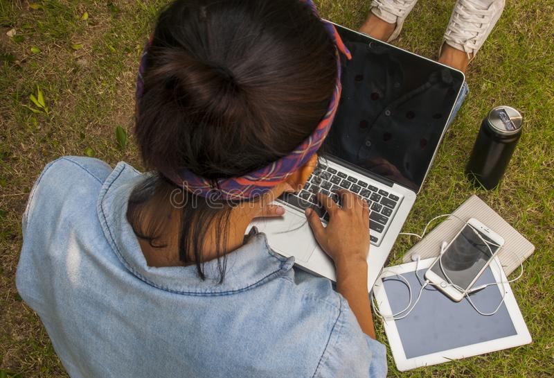 Women are using laptops in the garden. The top view of a woman sitting in a park on a green grass with a leptop and a tablet, a notebook and a cup of coffee next stock photography