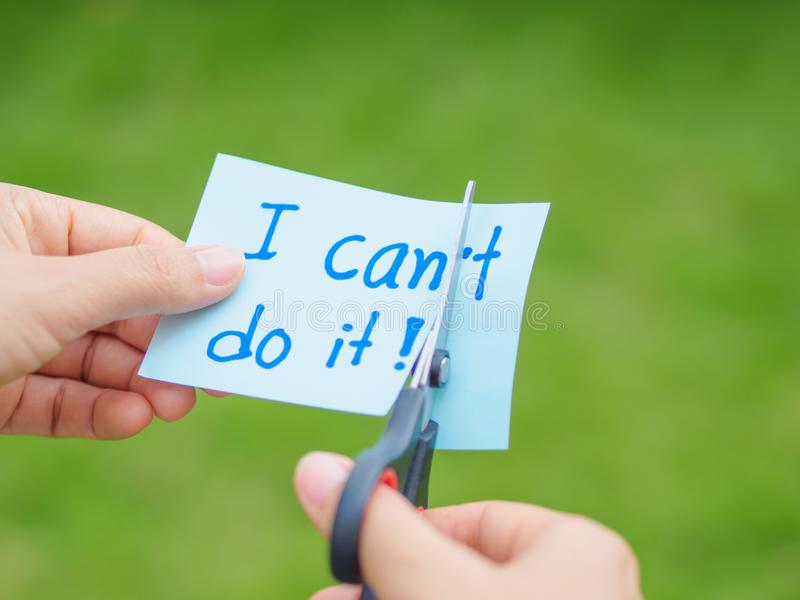Women using scissors to remove the word can`t to read I can do it concept for self belief, stock photo
