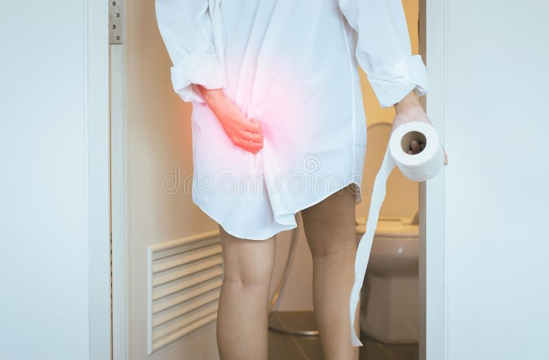 Women using toilet and suffers from Diarrhea and Hemorrhoids after wake up in morning at house. Woman using toilet and suffers from Diarrhea and Hemorrhoids stock image