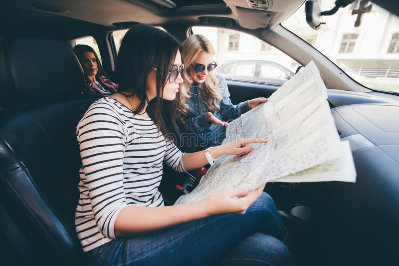 download women on vacation looking at map for directions while driving in car stock image