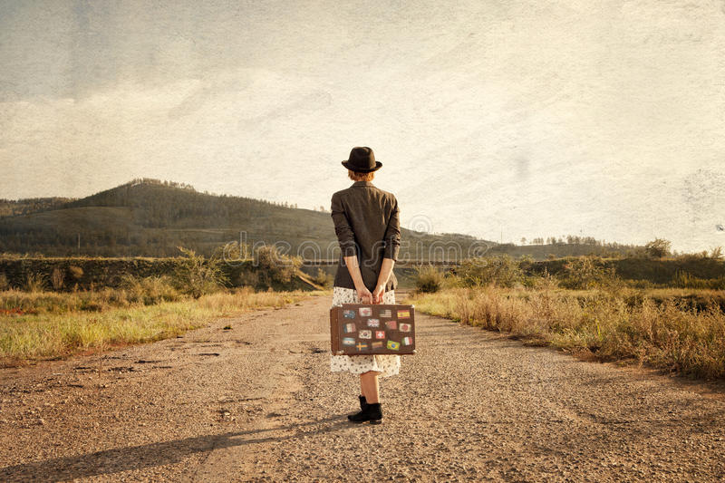 Women with vintage travel suitcase at old road. Photo in image s royalty free stock images