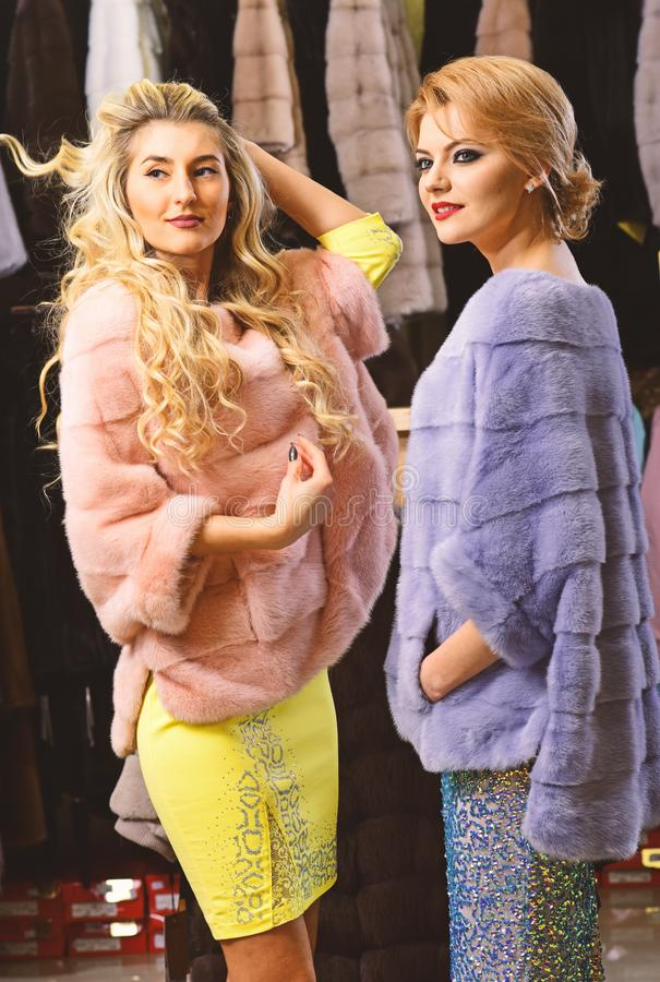 Women in violet and pink fur coats. Winter clothing concept. Ladies with blond hair in furry clothes in front of luxury store. Girls in fur coats with happy stock images