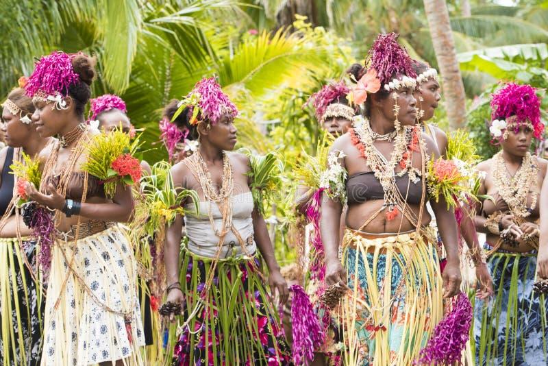 Costumed women waiting for dancing ceremony Solomon Islands between tropical vegetation royalty free stock photos