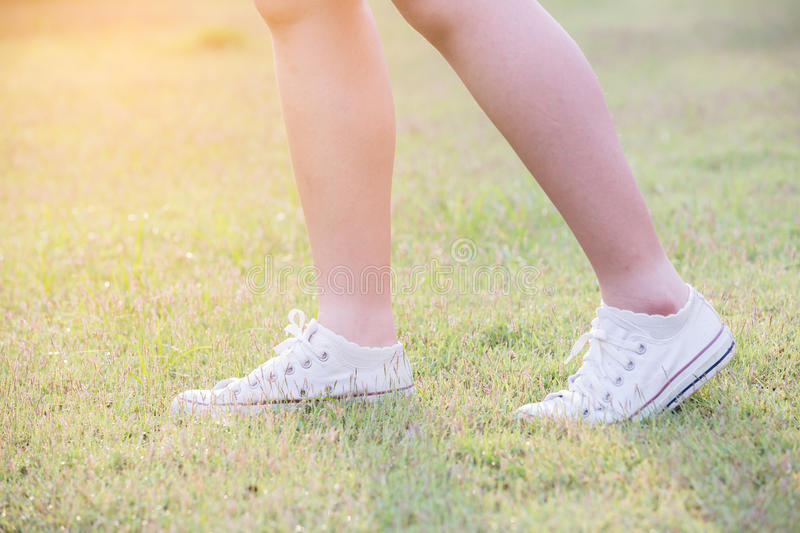 Women walk on grass. With sneakers stock photography