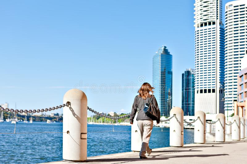 Women walk on the street near to a fence. Women walk or go to work on the street waterside with a concrete pillar fence next to the river and in the city royalty free stock photos