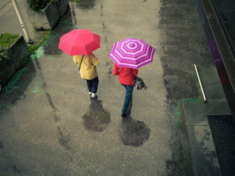 Women walk with an umbrella on a rainy, wet street. Colorful umbrella royalty free stock photos