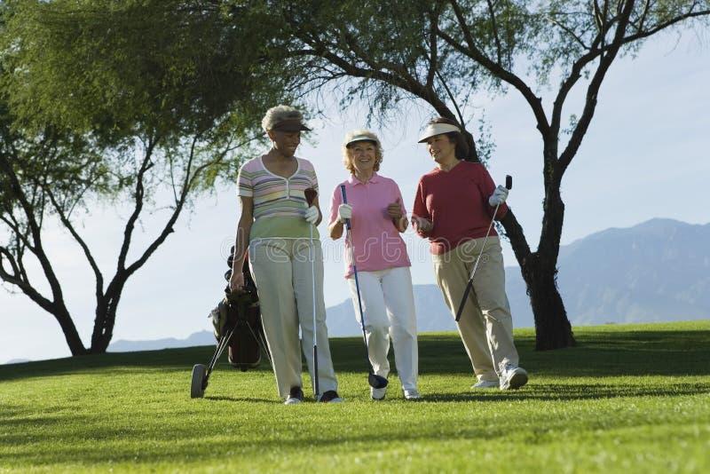Women Walking On Golf Course. Three mature women walking on golf course stock photography