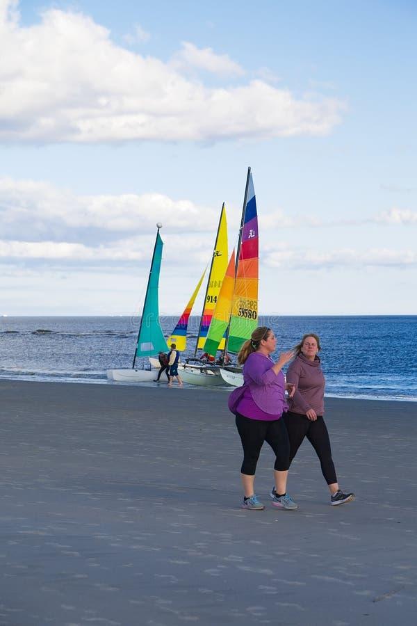 Women Walking Past Sailboats stock images