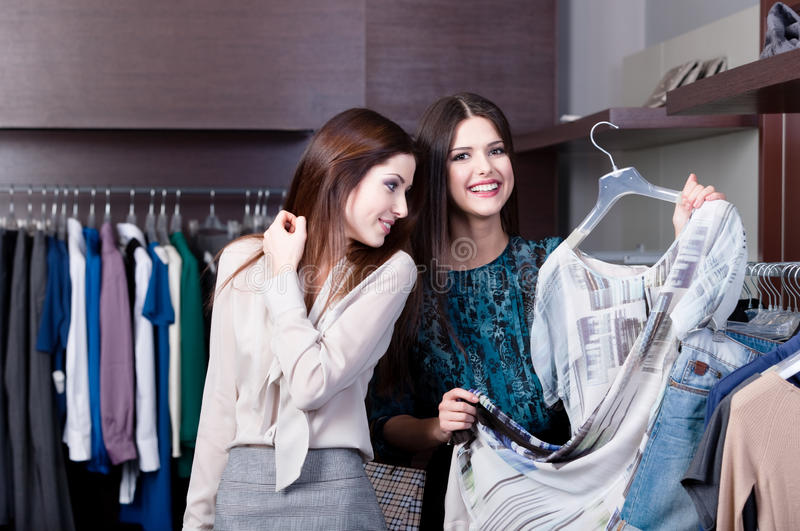 Women want to try on a dress. At the shop stock photography