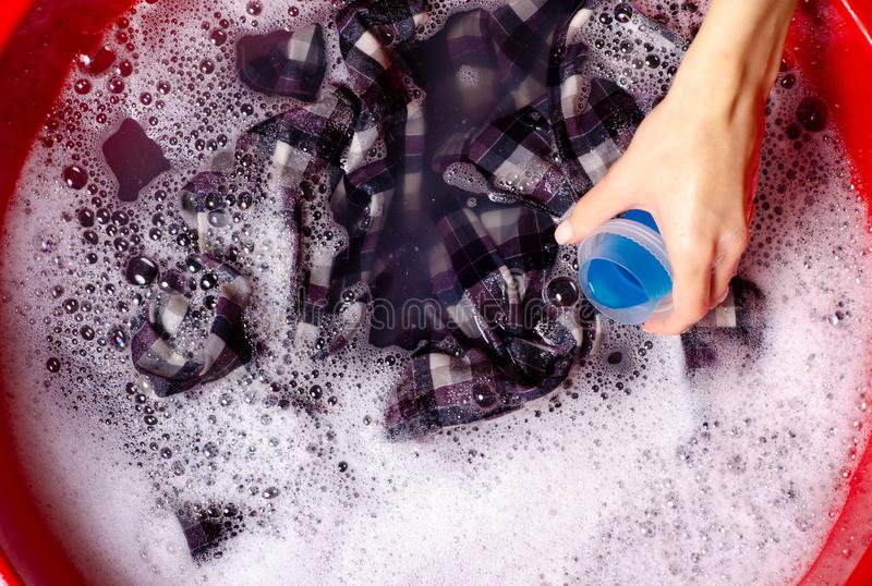 Women washing color clothes shirt in basin enemale powdered detergent liquid laundry gel. Top view royalty free stock image