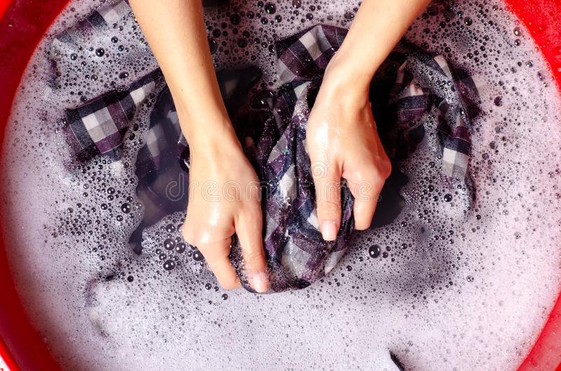 Women washing color clothes shirt in basin enemale powdered detergent. Top view stock image