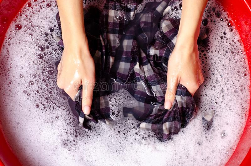 Women washing color clothes shirt in basin enemale powdered detergent. Top view royalty free stock images