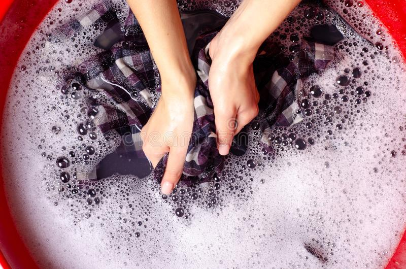 Women washing color clothes shirt in basin enemale powdered detergent. Top view royalty free stock photography