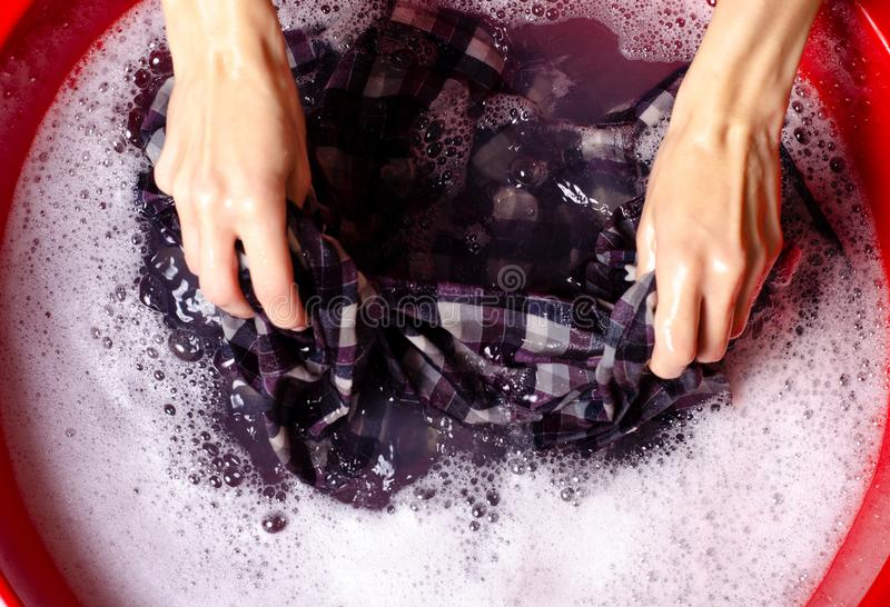Women washing color clothes shirt in basin enemale powdered detergent. Top view stock photography