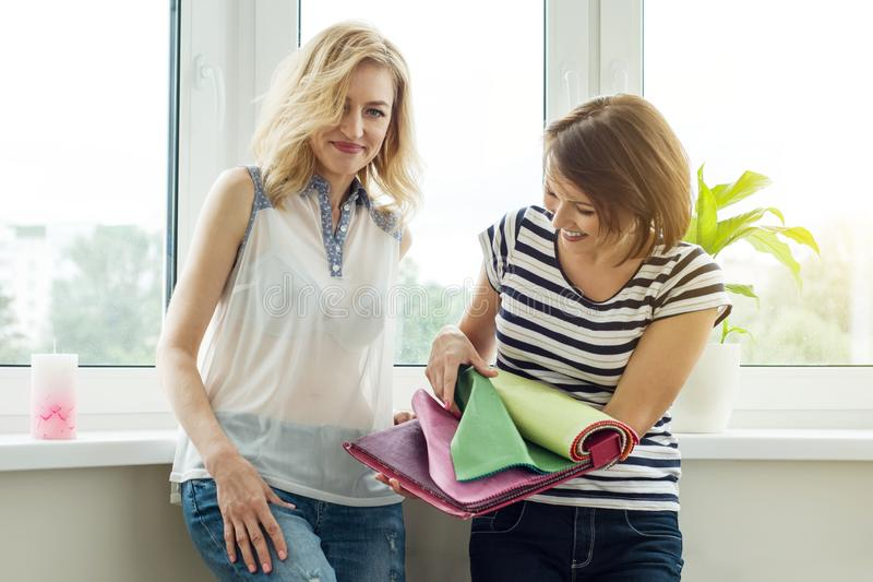 Women watch samples of fabrics for curtains, furniture upholstery new house. stock image