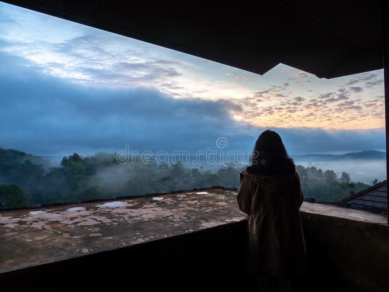 Women wear brown coat and standing on the balcony. And look outside with forest and mist in the morning. The golden sun is behind stock images