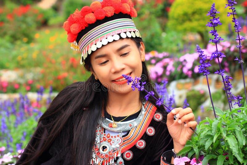 Women wear hill tribe costume. In flower garden stock photos