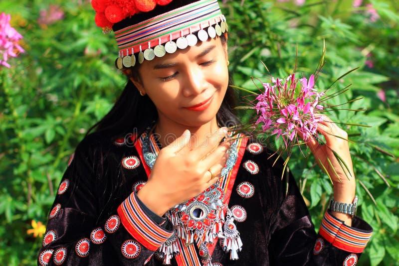 Women wear hill tribe costume. In flower garden stock images