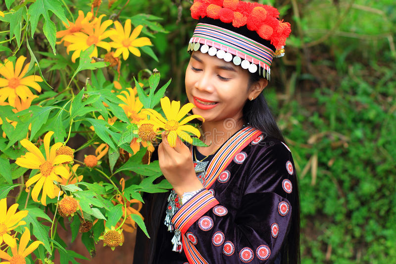 Women wear hill tribe costume with yellow flower. In garden stock images