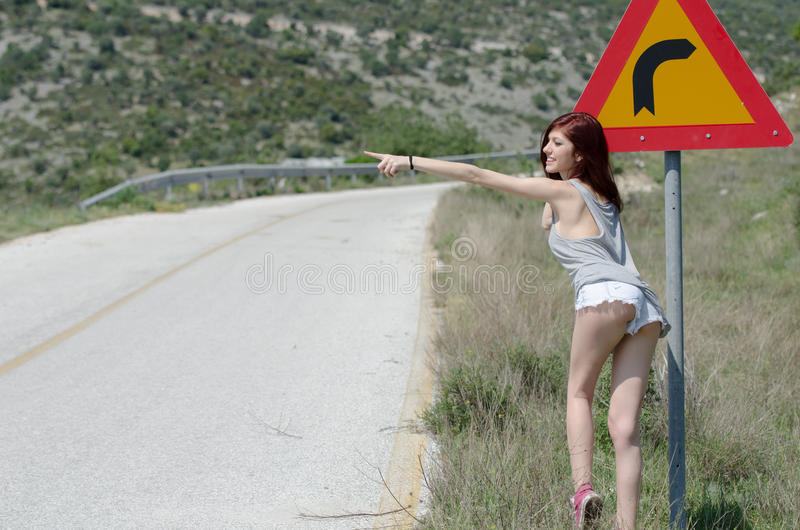 Women wear hot clothes hide a traffic sign danger turn royalty free stock photography