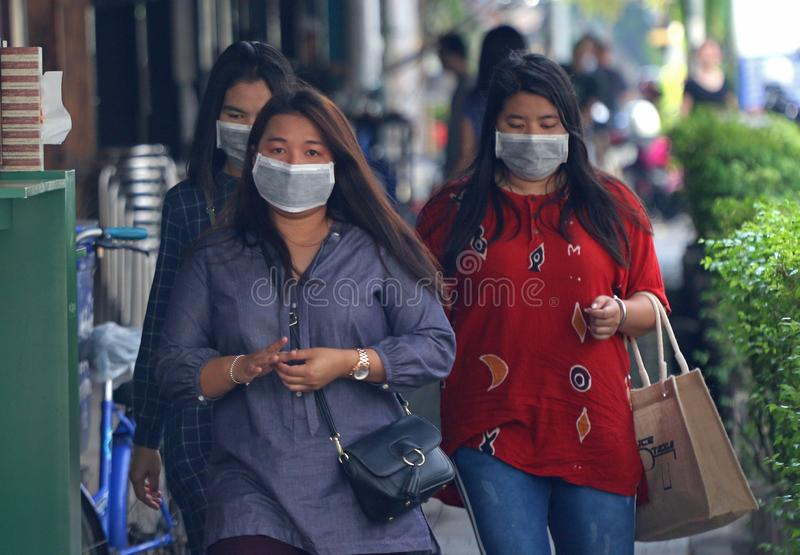 Women wear masks while walk on the street. Women wear masks while walk on the street during the unsafe levels of polluted air in Bangkok on January 26, 2019 stock photos