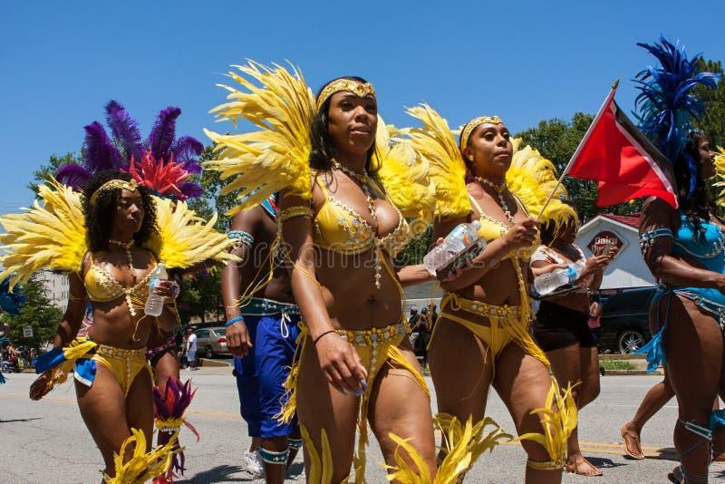 Women Wearing Bikinis Walk In Parade Celebrating Caribbean Culture. Atlanta, GA, USA - May 28, 2016: Women wearing yellow bikinis and elaborate feathered stock images