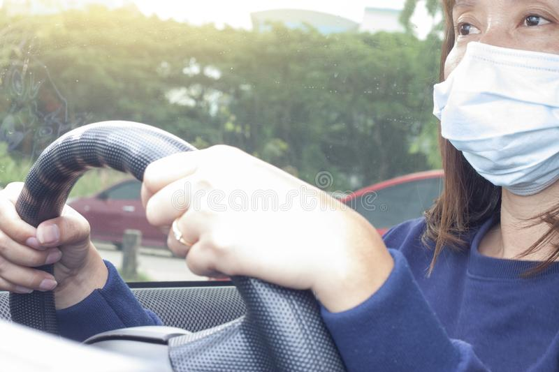 Women wearing face mask driving a car to hospital. stock photos