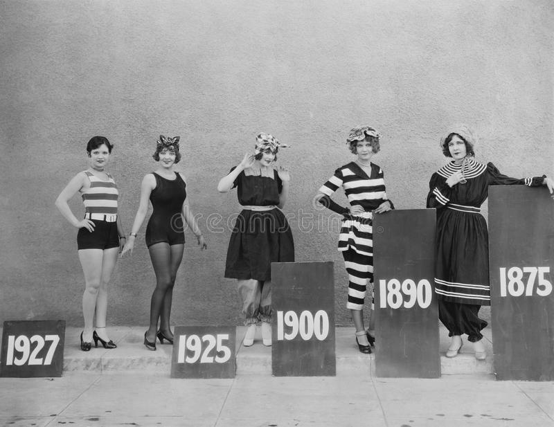 Women wearing fashions of different eras stock photography