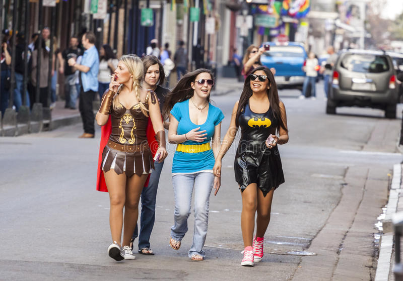 Women wearing funny costumes celebrating famous Mardi Gras carnival on the street in French Quarter. royalty free stock photography