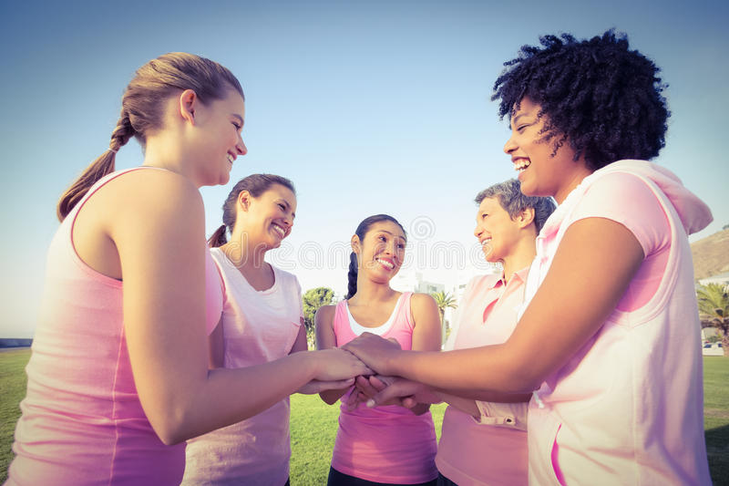 Women wearing pink for breast cancer and putting hands together. In parkland royalty free stock photo