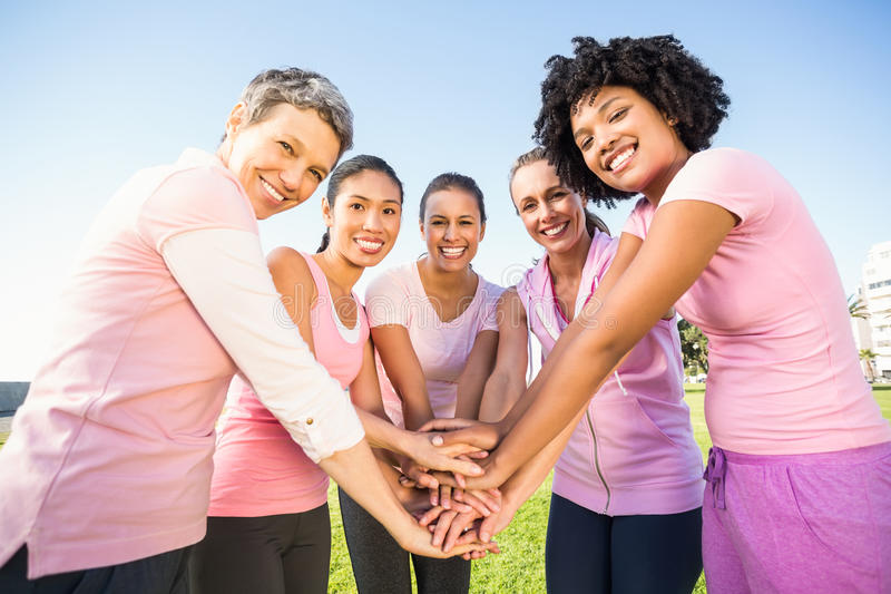 Women wearing pink for breast cancer and putting hands together. In parkland stock image