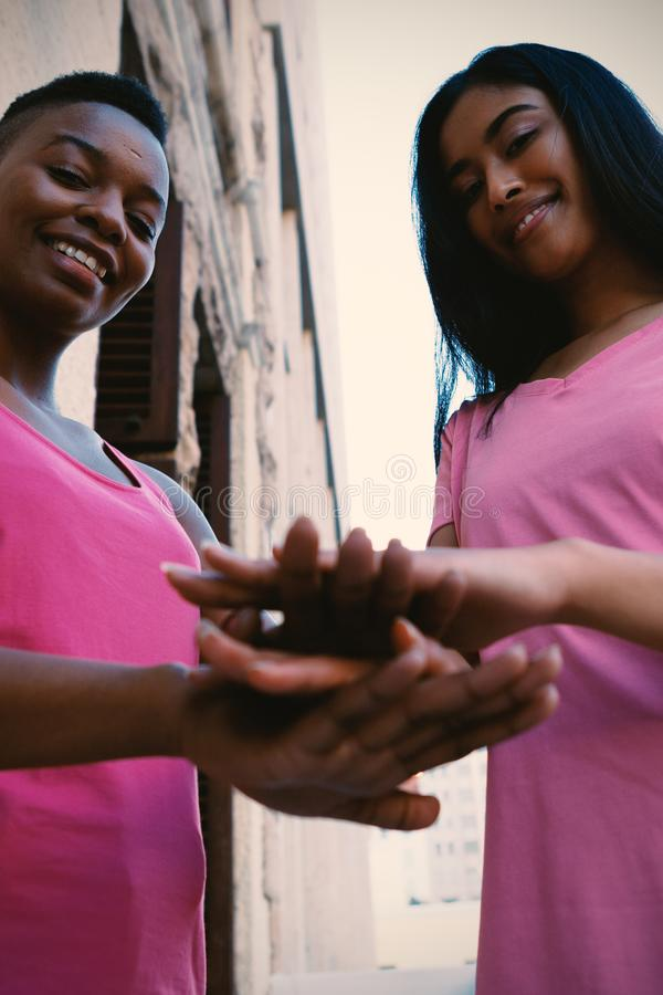 Women wearing pink for breast cancer and putting hands together royalty free stock photo