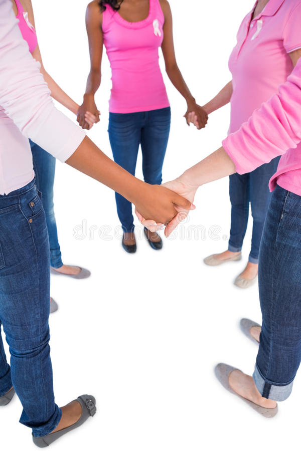Women wearing pink and ribbons for breast cancer holding hands i stock photo